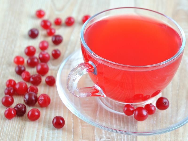 A cup of fresh cranberry juice on the table, next sprinkled cranberries